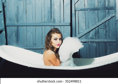 One beautiful sensual playful flirtatious young woman with long hair in blue knitted cloth sitting in white bath tub playing with soap foam indoor on wooden background, horizontal picture