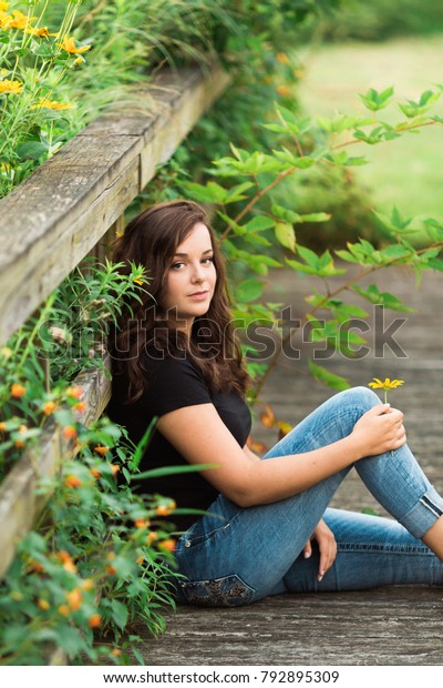 One beautiful teenage girl with brown hair outside on a beautiful summer day