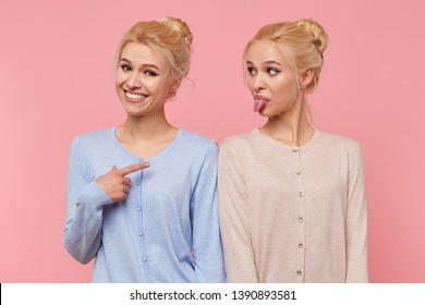 One of beautiful young blonde twins is fooling around and showing her tongue, her sister smiles broadly and pointing at her isolated over pink background.