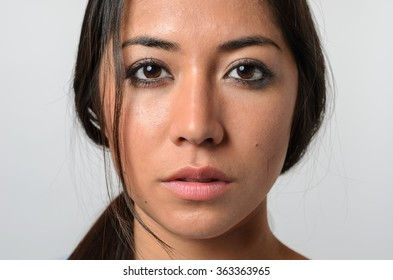 One beautiful young woman with stray hair and serious expression and blank stare