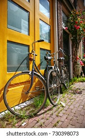One bicycle in front of modern orange building in urban European city on street sidewalk on sunny afternoon
