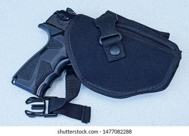 one big black gun in a holster lies on a gray table