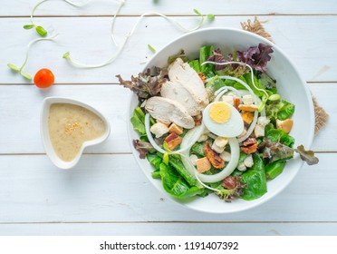 One big ceramic bowl of ceasar salad with ceasar dressing cream on white wood table.