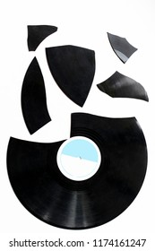 one big and many small pieces of broken vinyl on a white background. isolated