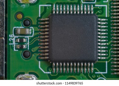 One big microscheme on green motherboard with a lot of legs. Close-up view.