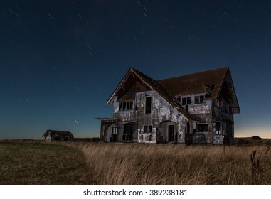 One big old house that is very run down at night.