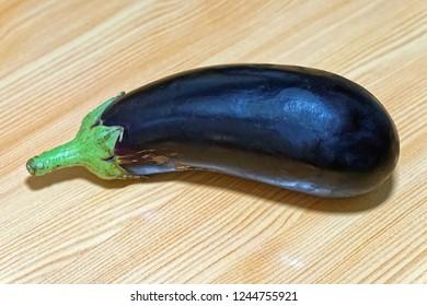 One big purple aubergine eggplant at table