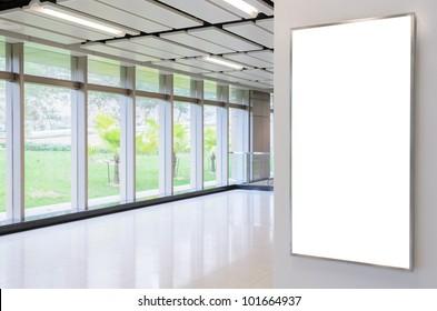 One big vertical / portrait orientation blank billboard on modern white wall with corridor background