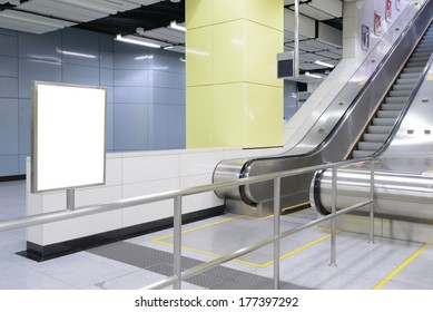 One big vertical / portrait orientation blank billboard in public transport with escalator and blurred passenger background