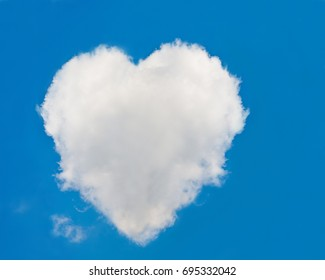 One big white cloud in the shape of a heart in the blue sky