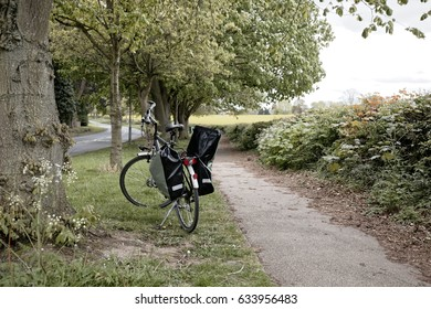 one bike with panniers on grass near path