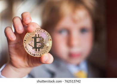 One Bitcoin in the hand of young boy. Concept.