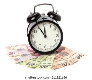 One black alarm clock on Mexican Pesos banknotes isolated on white.
