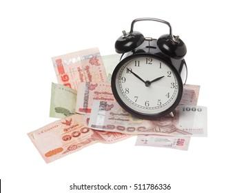 One black alarm clock on Thai baht banknotes isolated on white.