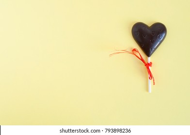 One Black chocolate candy in the shape of a heart on a stick, bandaged with a orange ribbonon a light yellow background. Card to the Valentine's Day.