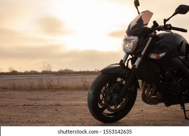 One black motorcycle in the desert in autumn time.
