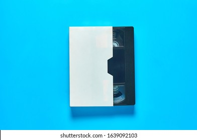 One black old vhs video cassette in white cardboard packaging on blue desk. Concept of 90s. Top view. Close-up