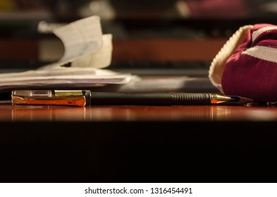One black pencil and a pink pencilcase on the wooden  table from the side view. School supplies or stuff. Education or business concept.