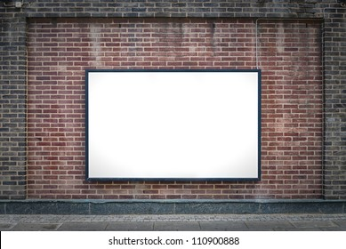 one blank billboard attached to a buildings exterior brick wall.