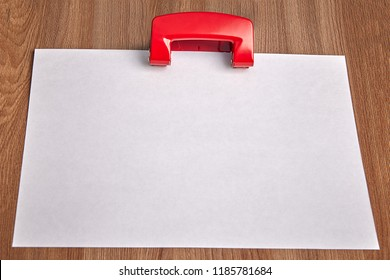 One blank sheet of white paper is clamped in steel red office hole puncher on background of wooden table, mockup with copy-space.