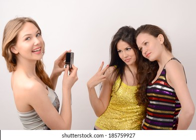 One blonde and two brunette women having fun, blonde woman photographing and smiling a couple of brunette women