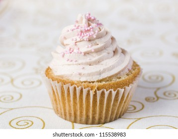 One blue cupcake on a  tablecloth. The cupcake is a tasty dessert.
