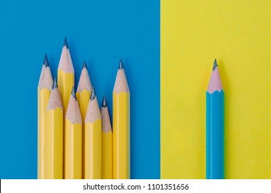 One blue pencil on yellow background and group of yellow pencils on blue background. Individuality and difference concept.