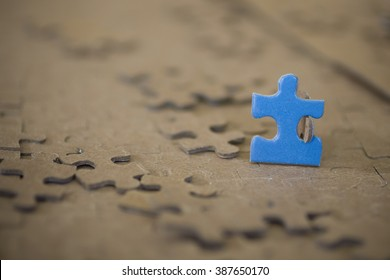 One Blue Puzzle Piece Standing Alone with Blurred background