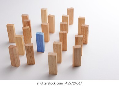 One blue wood block outstanding and different in crowd, metaphor to business concept of being differentiate, individual, leadership, or outstanding. Selective focus, gray background.