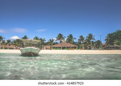 One boat floating in the transparent sparkling ocean water against background with white sand beach,palm forest  and luxury bamboo huts,clear blue sky on a sunny summer day.Panglao island,Philippines.