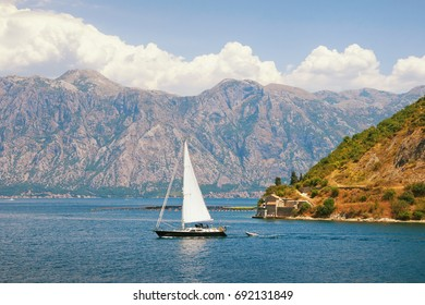 One boat sails along Kotor Bay on a summer day. Montenegro