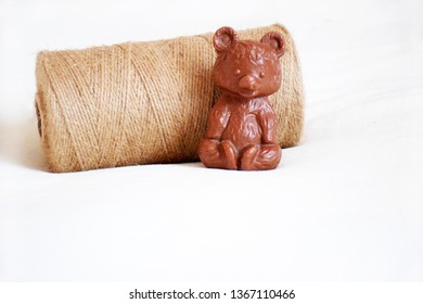 One bobbin with natural linen rope and brown small bear toy with copy space for text.  Coil natural twine with a closeup, selective focus.