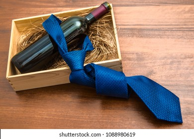 one bottle of red wine with blue tie in wooden box on wood table background. empty copy space for object or inscription. Father's day holiday idea, sign, symbol, concept.