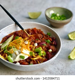 One bowl of homemade organic chili con carne served with grated cheddar cheese, scallions and sour cream, extra scallions and lime wedges. Traditional Mexican dinner, square photo.