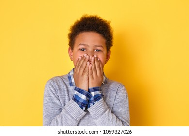 One boy studio isolated on yellow wall covering mouth