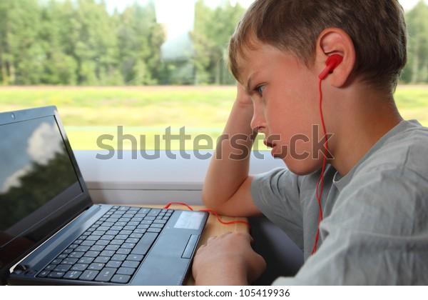one boy watches movie on laptop in train