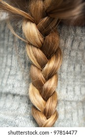 One braid of light hair of a young girl