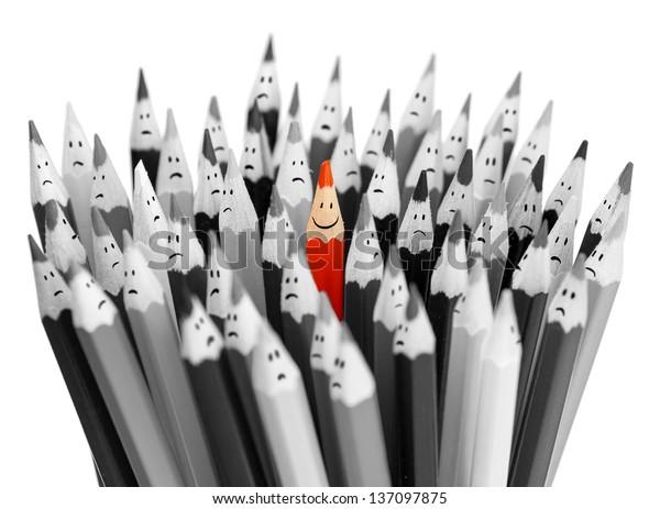 Un lápiz sonriente de color brillante entre un montón de lápices grises tristes