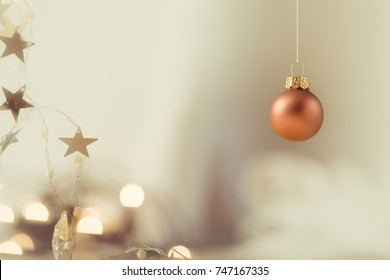 one bright copper colored Christmas ball, with soft light background