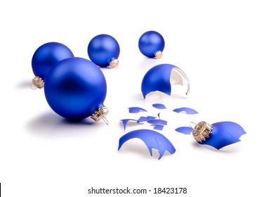 One broken blue Christmas Tree ornament and four intact on a field of white.