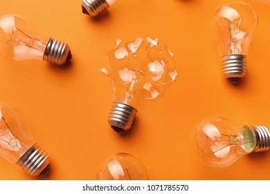 One broken light bulb among whole ones on yellow background, side view, closeup. Creativity and fragility concept