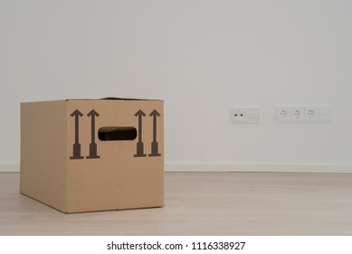 One brown package card box in empty white room with windows and wooden flooring, electric outlets in background - Moving Day
