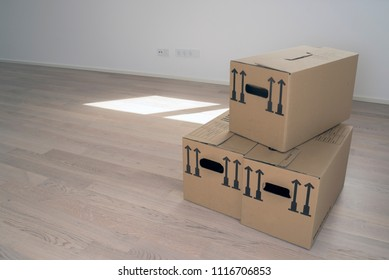 One brown package card box in empty white room with windows and wooden flooring, windows and door in background - Moving Day