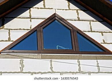 one brown triangular window on a white brick wall of the attic of a private house