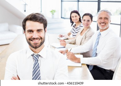 One businessman is standing and three workers are sitting and smiling at work