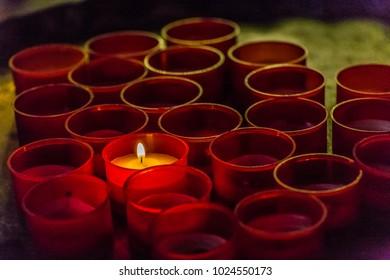 one candle burning amongst extinguished ones