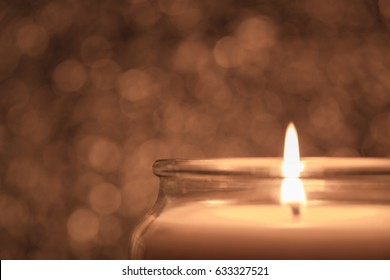 One candle with the flame in focus and a dramatic, golden bokeh background, horizontal format, copy space.
