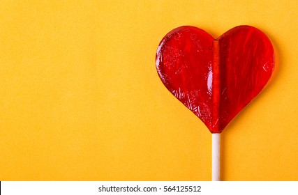 One candy heart shape on yellow background