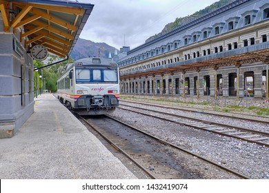 One car train waiting in station on small platform next to the former abandonned one from the town's glory days. Canfranc Estacion, Spain, May 28, 2019
