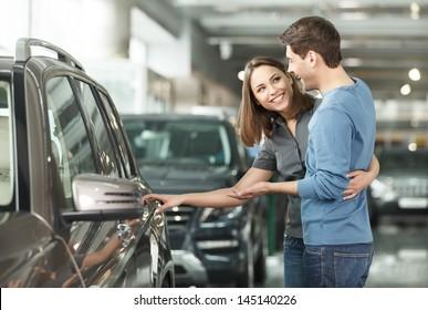 ¡Es el auto que quiero! Hermosa pareja joven parada en el concesionario eligiendo el auto para comprar
